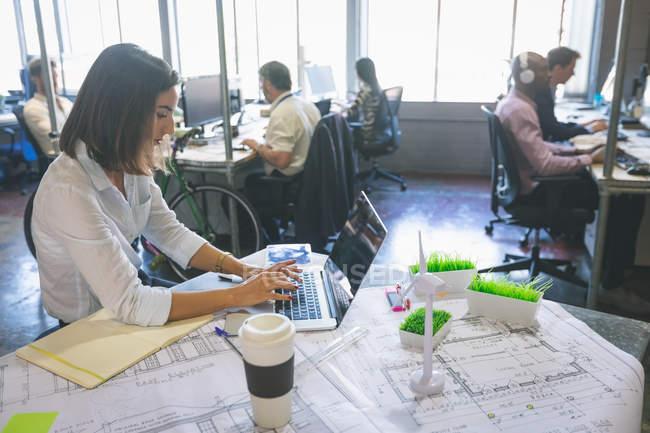 Жіночий виконавчий, використовуючи ноутбук на столі в офісі — стокове фото