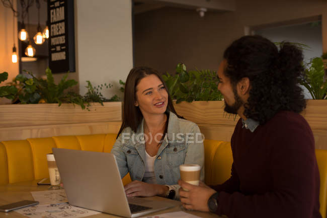 Couple souriant se parlant dans un café — Photo de stock