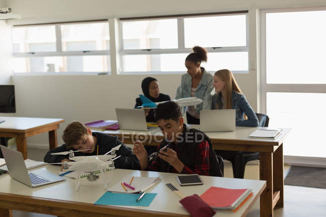 Students discussing together over model aeroplane in training institute — Stock Photo