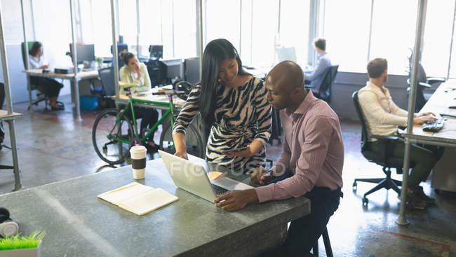I colleghi d'affari discutono sopra computer portatile in sala conferenze a ufficio — Foto stock