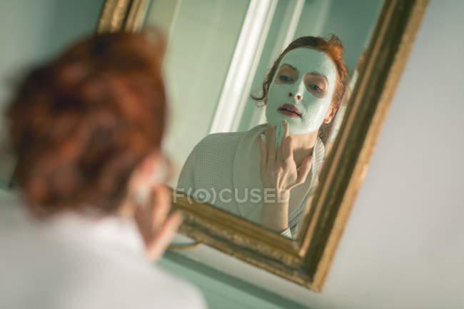 Frau trägt Gesichtsmaske vor Spiegel im Badezimmer auf — Stockfoto