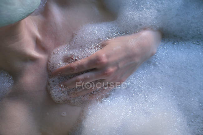 Mid section of woman relaxing in bathtub at bathroom — Stock Photo