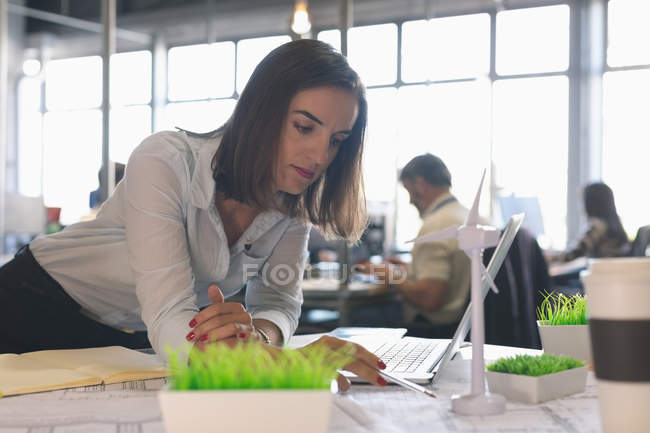 Female executive looking at windmill model in office — Stock Photo