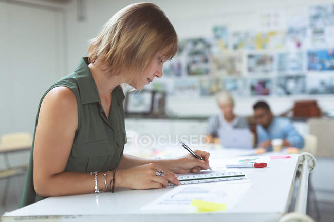 Side view of female executive working on drafting table in office — Stock Photo