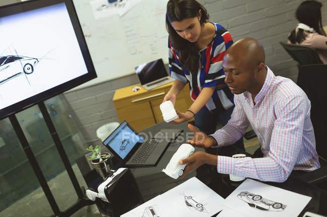 Коллеги по бизнесу обсуждают модель автомобиля в офисе — стоковое фото