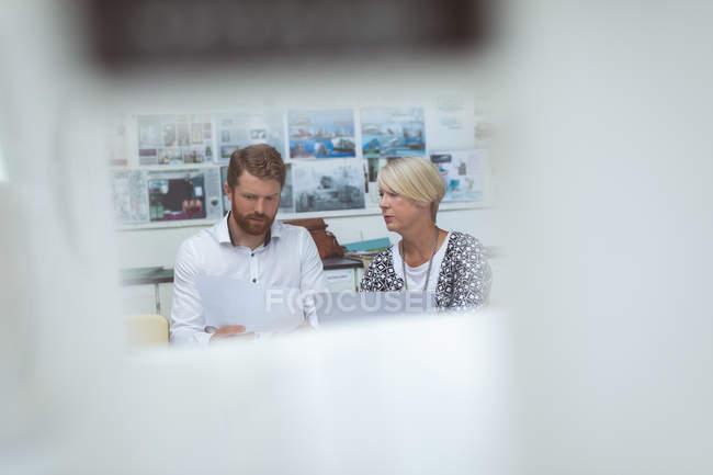 Executivos discutindo sobre o documento na mesa no escritório — Fotografia de Stock