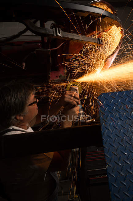 Male mechanic using grinder machine in garage — Stock Photo
