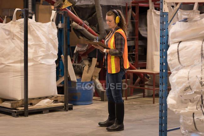 Trabajadora, escribir en el portapapeles en almacén - foto de stock