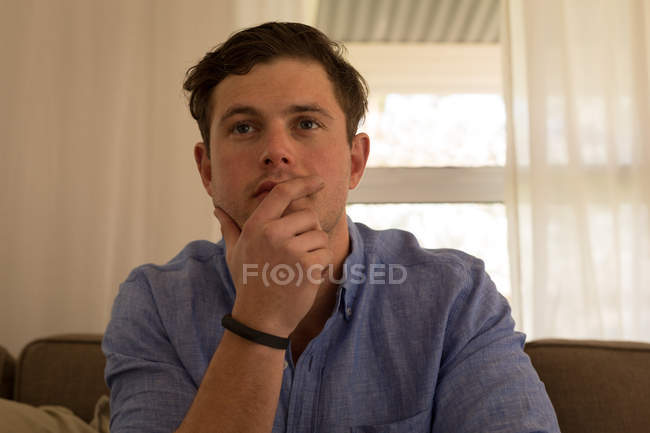 Man watching television in living room at home — Stock Photo
