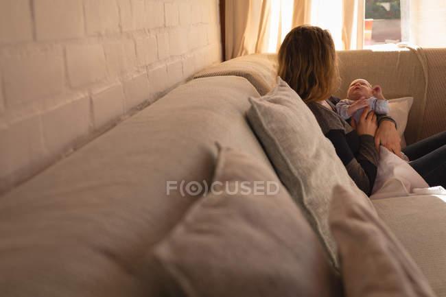 Mamma culla il suo bambino sul divano di casa — Foto stock