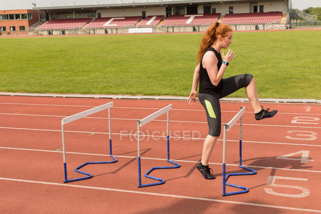 Female athlete exercising over hurdles on running track — Stock Photo