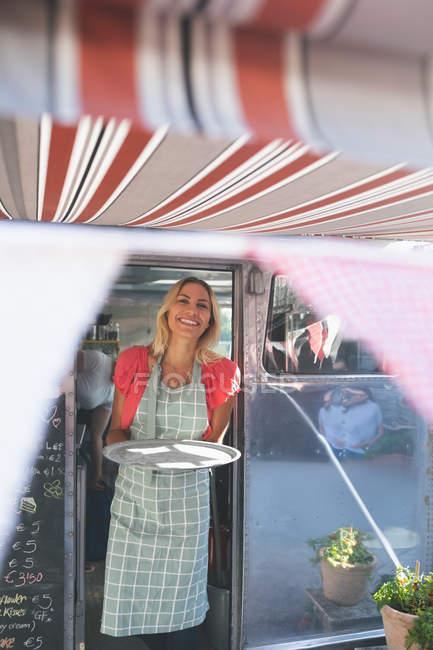 Жіночий офіціантка, стоячи в харчової вантажівка — стокове фото