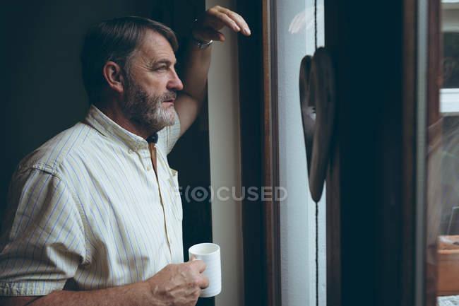 Продуманий старший чоловік з чашки кави, переглядаючи вікна будинку — стокове фото