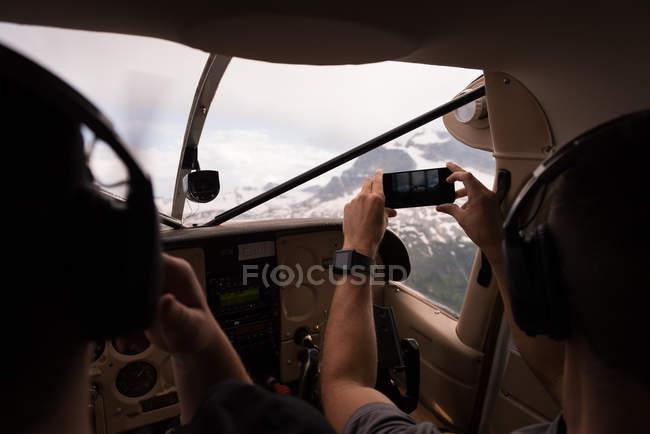 Piloto tomando fotos con el teléfono móvil durante el vuelo en cabina de avión - foto de stock