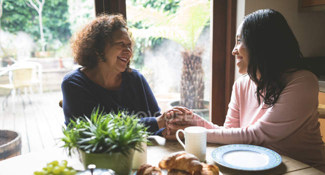 Mother and daughter consoling each other on dinning table at home — Stock Photo