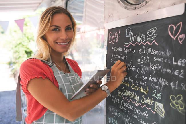 Portrait of female waitress writing menu on menu board while using digital tablet — Stock Photo