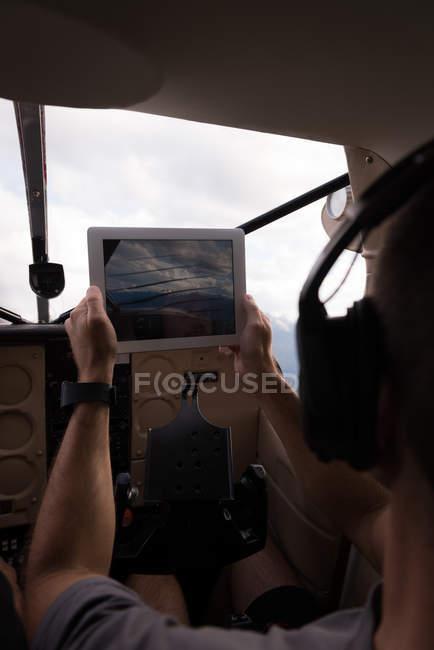 Piloto tomando fotos con tabla digital durante el vuelo en cabina de avión - foto de stock