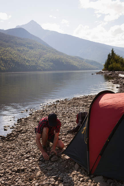 Man setting up tent near riverside in mountains — Stock Photo