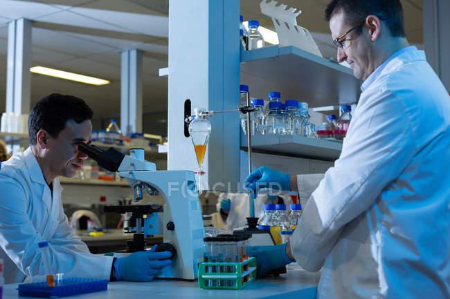 Cientistas masculinos juntos a fazer experiências no laboratório — Fotografia de Stock