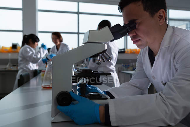 Cientista masculino usando microscópio em laboratório — Fotografia de Stock