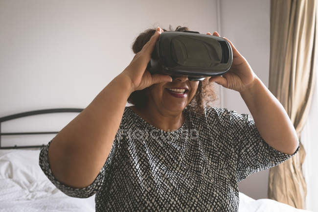 Senior woman using virtual reality headset in bedroom at home — Stock Photo