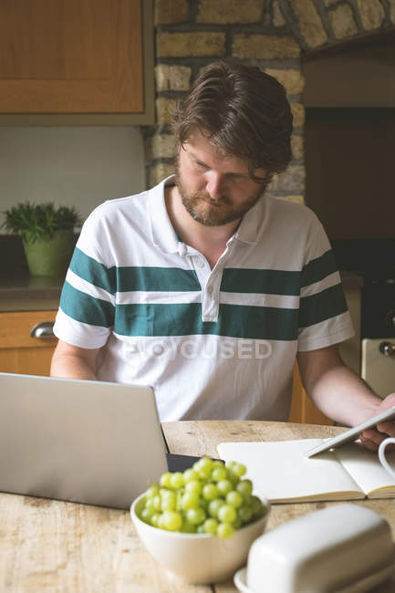 Man using laptop in kitchen at home — Stock Photo