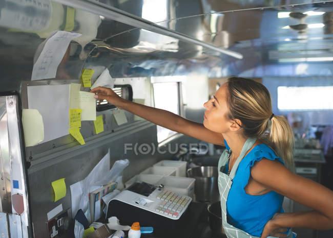 Camarera mujer mirando órdenes en papelitos en el carro de comida - foto de stock