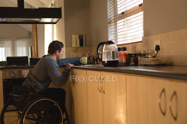 Disabled man preparing coffee in kitchen at home — Stock Photo