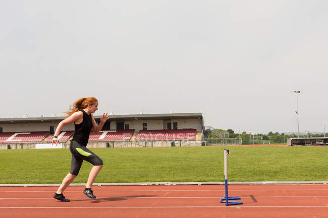 Young female athletic running over hurdle on sports track — Stock Photo