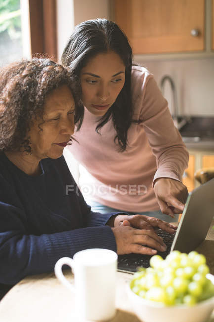 Mother and daughter discussing over laptop at home — Stock Photo