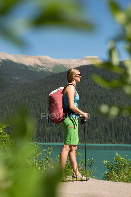 Female hiker standing near riverside in mountains — Stock Photo