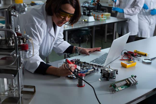 Female scientist soldering circuit board in laboratory — Stock Photo
