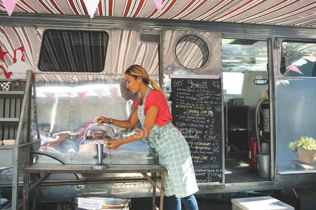 Вид збоку жіночий офіціантка роботі поблизу харчової вантажівка — стокове фото