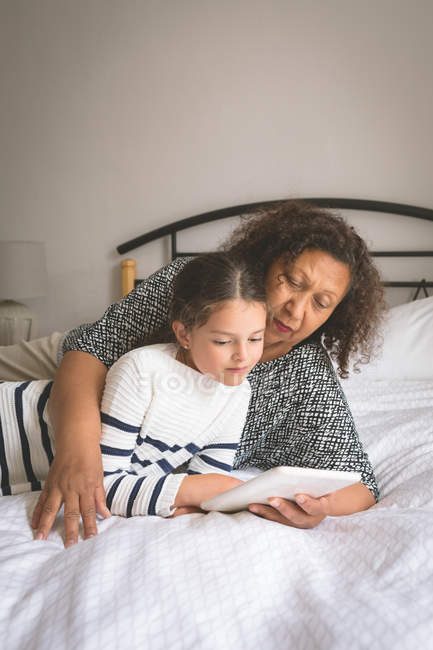 Grandmother and granddaughter using digital tablet in bedroom at home — Stock Photo