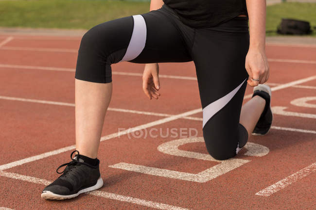 Low section of female athletic exercising on running track — Stock Photo