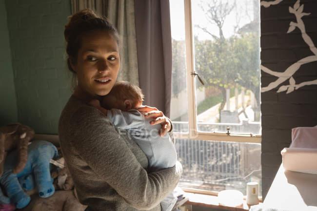 Мать ребенка Холдинг возле окна дома — стоковое фото