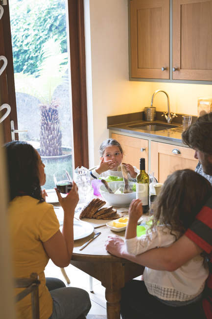 Family having a meal on dining table at home — Stock Photo