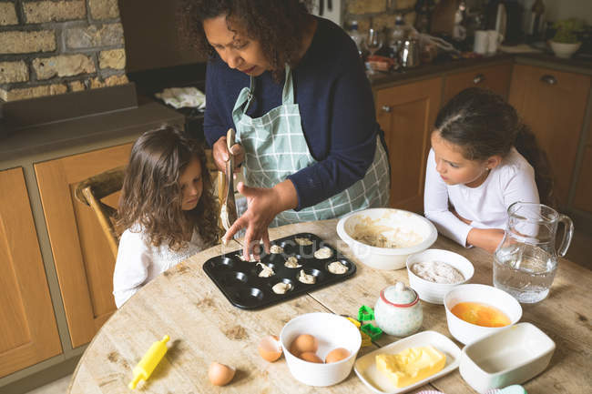 Grandmother with her granddaughters preparing breakfast on dining table at home — Stock Photo