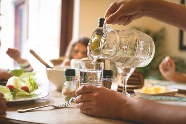 Primer plano del hombre que sirve agua en vidrio en la mesa de comedor en hom - foto de stock