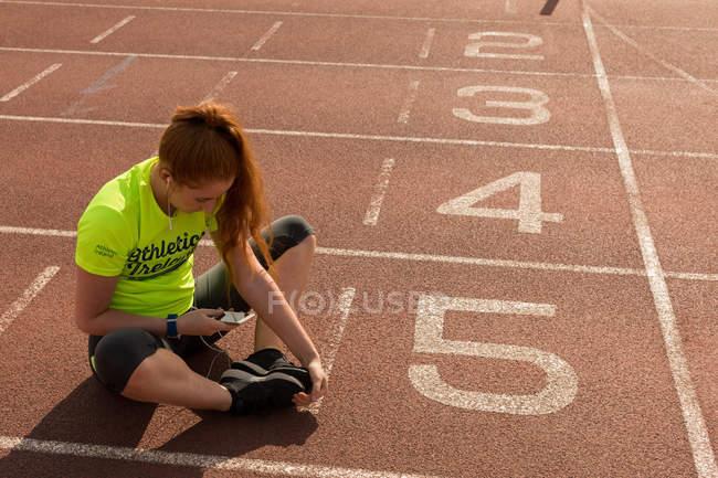 Jeune athlète féminine utilisant un téléphone portable tout en faisant de l'exercice sur piste de course — Photo de stock