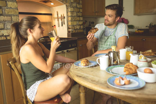 Couple having breakfast and juice on dinning table at home — Stock Photo