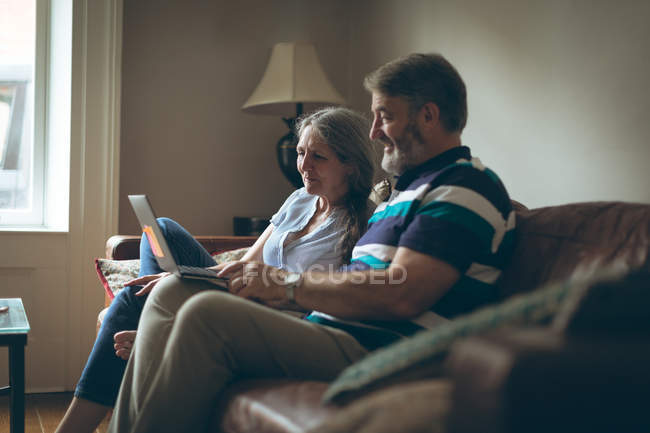 Старшая пара использует ноутбук в гостиной на дому — стоковое фото