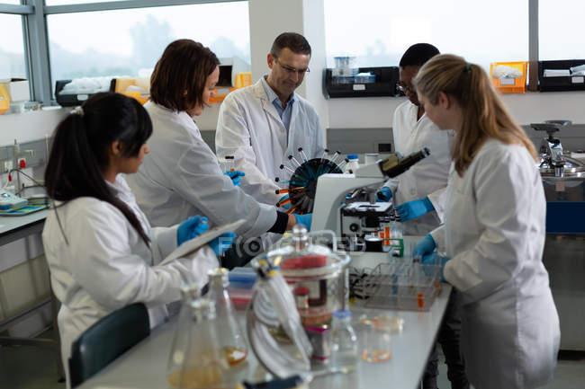 Équipe de scientifiques expérimentant ensemble en laboratoire — Photo de stock