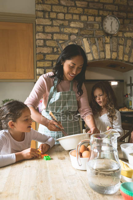 Mother cooking food with her daughters at home — Stock Photo