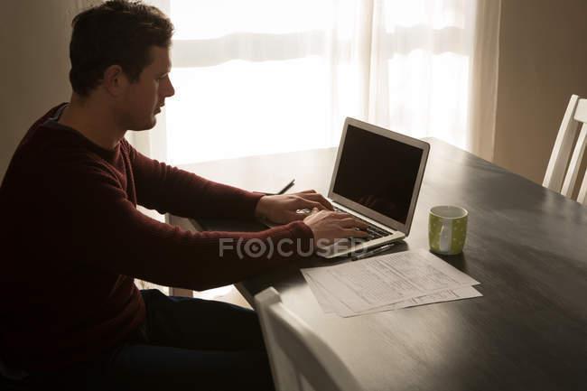 Homme handicapé à l'aide de portable sur la table à manger à la maison — Photo de stock