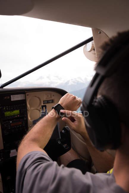 Piloto que utiliza smartwatch durante o voo no cockpit da aeronave — Fotografia de Stock