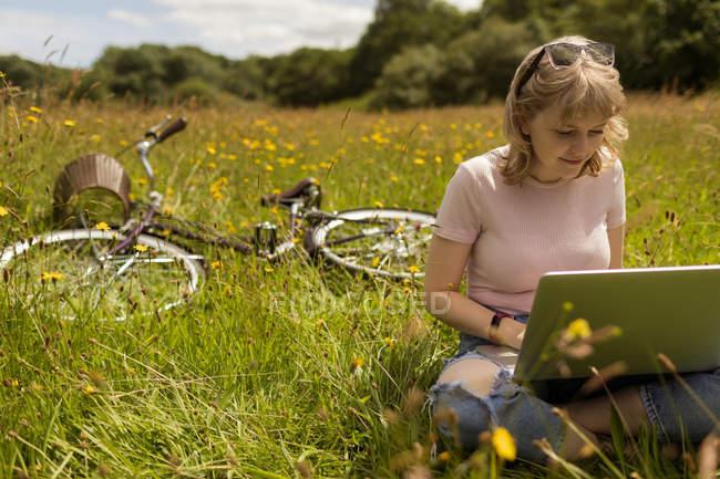 Junge Frau mit Laptop im Feld — Stockfoto