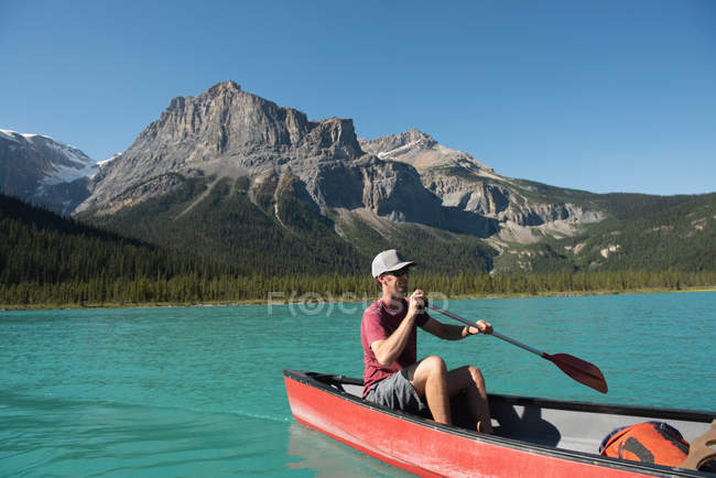 Man rowing a boat on river in mountains — Stock Photo