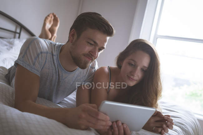 Couple utilisant une tablette numérique dans la chambre à coucher à la maison — Photo de stock