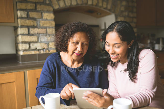 Mother and daughter using digital tablet at home — Stock Photo